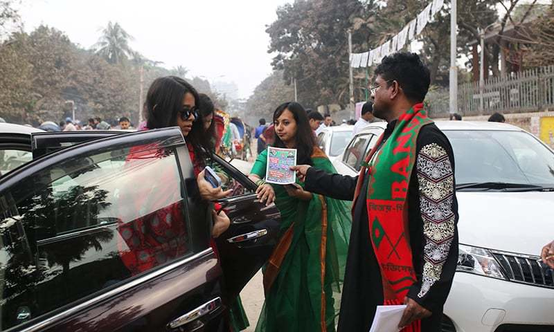 Supporters of the ruling Bangladesh Awami League distribute leaflets to people voters during the general election campaign in Dhaka. — AFP