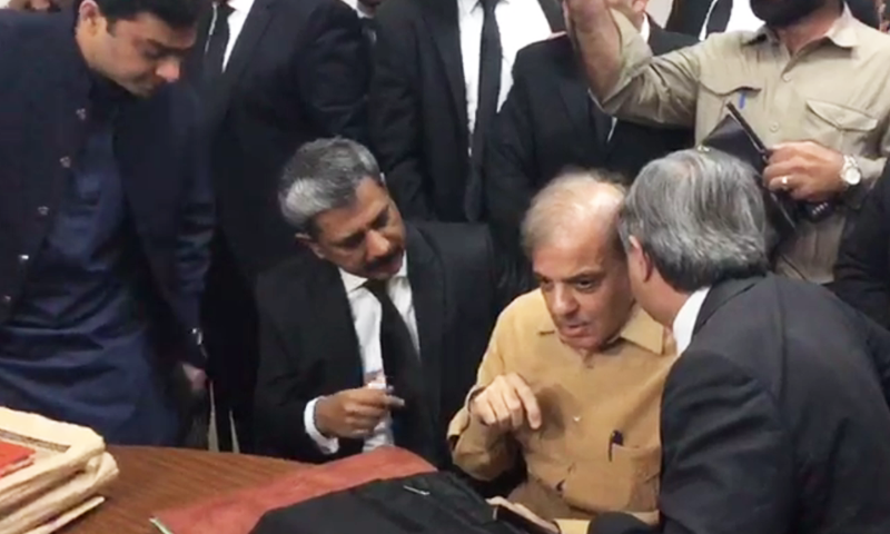 PML-N President Shahbaz Sharif talks to lawyers ahead of a hearing of the Ashiana scam in an accountability court. — File photo