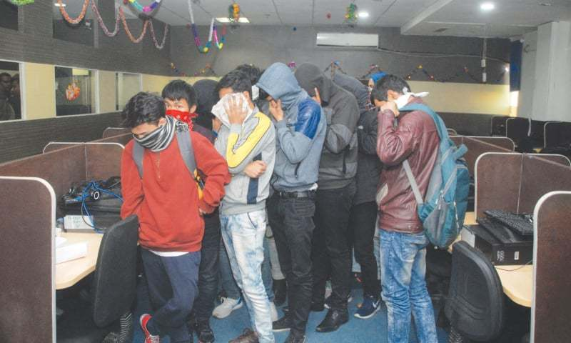 New Delhi: Workers of the fake call centre cover their faces during police raid in Noida, 25 kilometres east of  New Delhi.—AFP