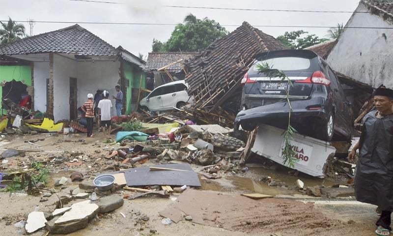 CARITA: People look at the destruction in a tsunami-ravaged neighbourhood.—AP