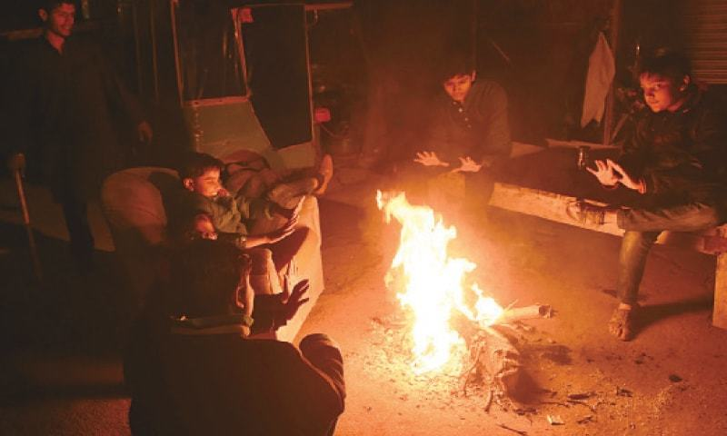 Children use logfire to keep themselves warm on a road. Bonfires and bon mots go hand in hand during peak winter days. — White Star / M. Arif