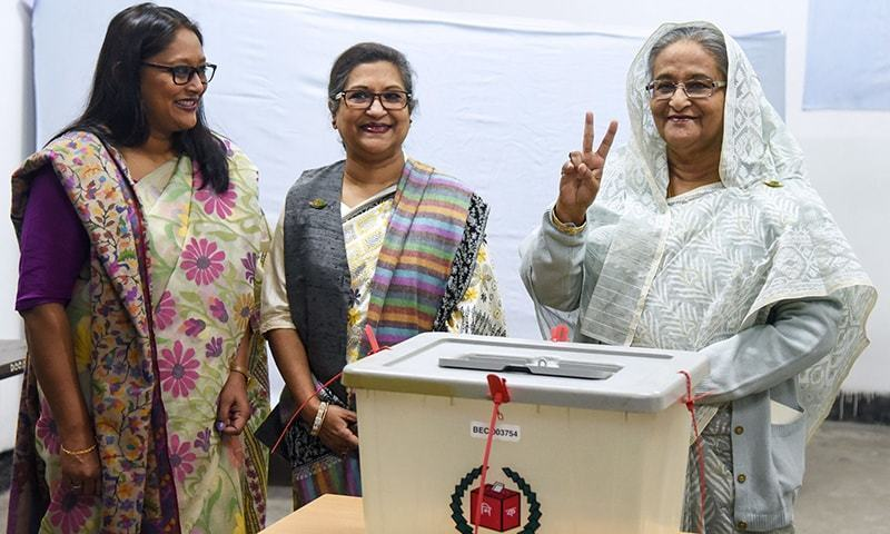 Bangladeshi Prime Minister Sheikh Hasina (R) flashes the victory symbol after casting her vote, as her daughter Saima Wazed Hossain (1st L) and her sister Sheikh Rehana (2nd L) look on at a polling station in Dhaka on Sunday. — AFP