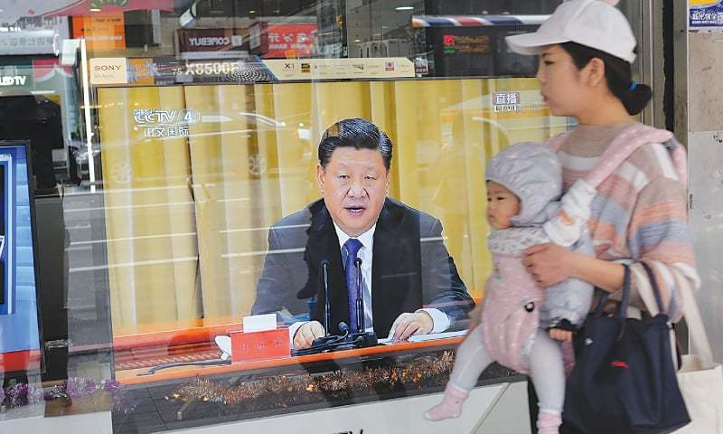 TAIPEI CITY: A mother carries her child past a television set showing China's leader Xi Jinping making a speech on Wednesday in which he warned against efforts to promote the island's independence.—AFP