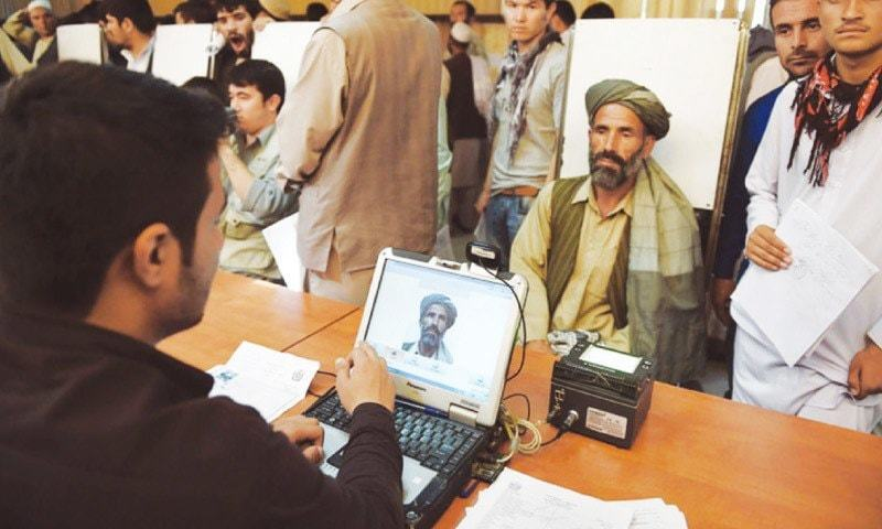 A man has his photograph taken at the passport office in Kabul.—AFP/File