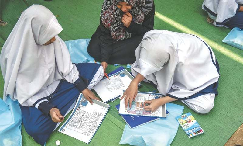 a group of schoolgirls busy making drawings of old buildings on Thursday.—White Star