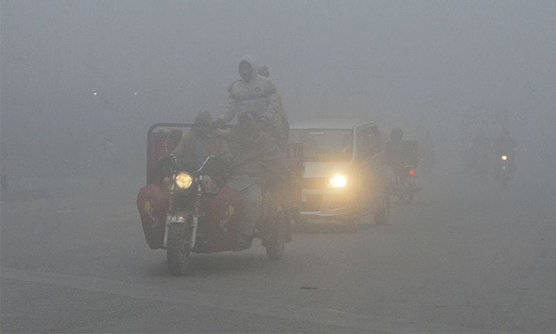 LAHORE: Commuters drive their vehicles on a road amid heavy smog on Thursday. Smog levels often spike during winter in Punjab, making driving difficult and even dangerous. But on Wednesday and Thursday the weather conditions caused several feeders in the provincial capital to trip, cutting electricity supply to many areas.—AFP