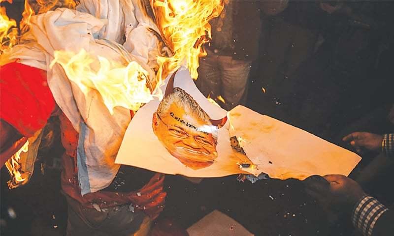 NEW DELHI: Protesters burn a poster of Kerala Chief Minister Pinarayi Vijayan during a demonstration on Thursday.—AFP