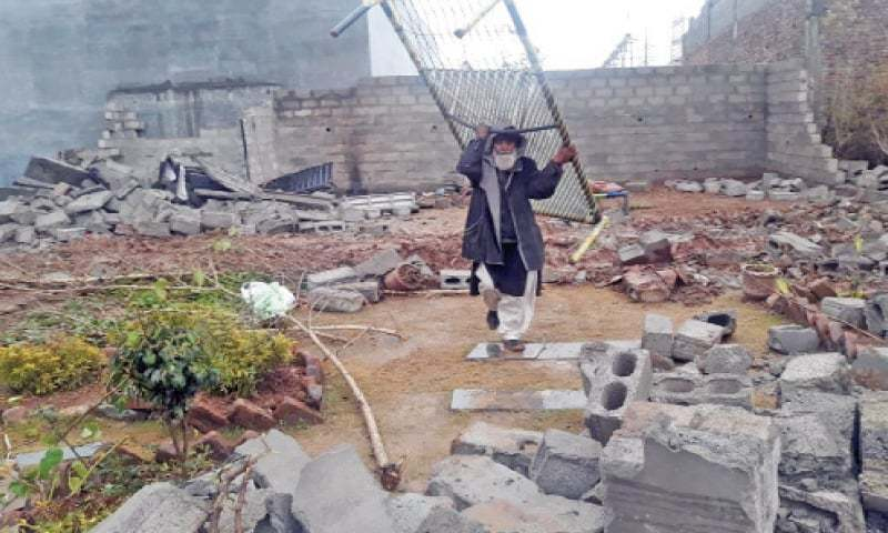 A man carries his charpoy from the debris of his demolished house after the operation on Saturday. — Dawn