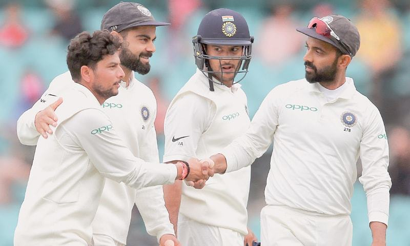 INDIA'S bowling hero Kuldeep Yadav (left), is congratulated by team-mates after taking five wickets against Australia in the fourth and final Test at the SCG on Sunday.—AP