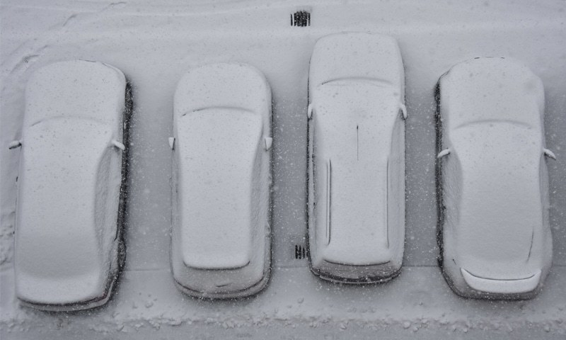 Bratislava (Slovakia): Parked cars are covered by snow during heavy snowfall on Tuesday.—AP