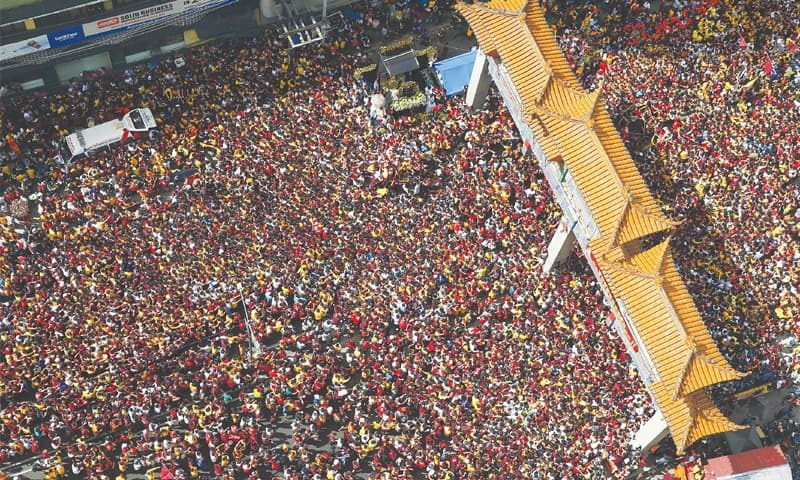 MANILA: A massive crowd of devotees follow the carriage of the Black Nazarene during a raucous procession to celebrate its feast day on Wednesday.—AP