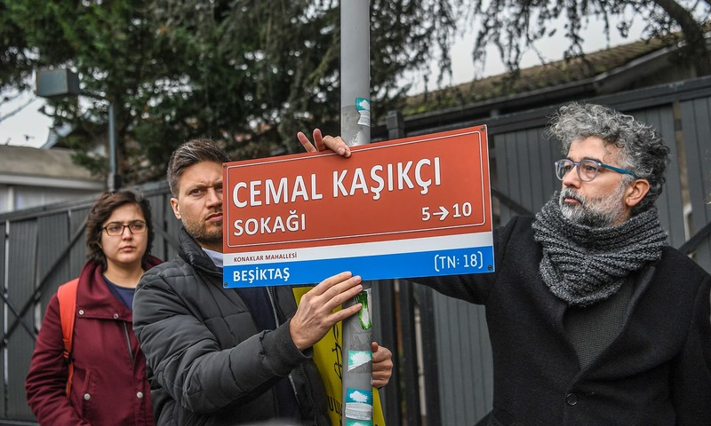 """Andrew Gardner, Amnesty International's Turkey Researcher (L), and Erol Onderoglu, Turkey representative for international rights group Reporters Without Borders (RSF) hang a street sign reading """"Jamal Khashoggi street"""",  in the street of Saudi Arabian consulate. —AFP"""