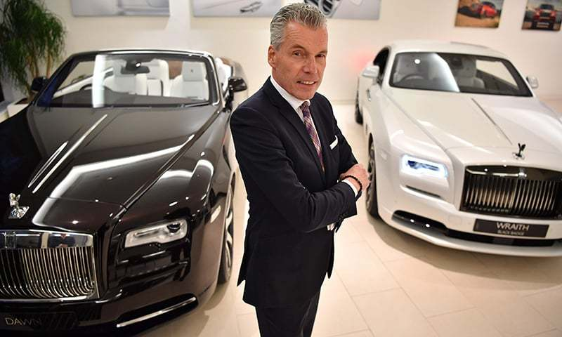 Rolls-Royce Motor Cars German CEO Torsten Muller-Otvos poses with a Rolls-Royce Dawn (L) and Rolls-Royce Wraith Black Badge (R) cars in a showroom in central London on January 9, 2019. —AFP