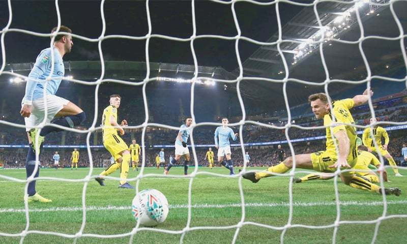 MANCHESTER: Manchester City's Phil Foden (second R) scores during the English League Cup semi-final first leg against Burton Albion at the Etihad Stadium.—Reuters