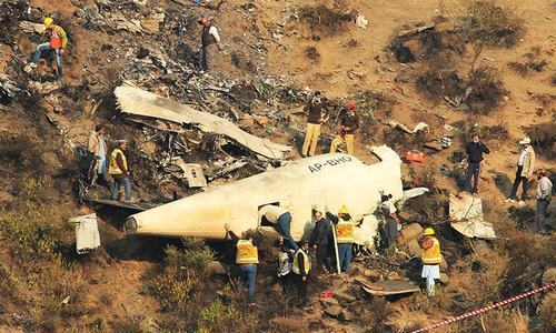 Rescue workers survey the site of a plane crashed near the village of Saddha Batolni.— Reuters/File