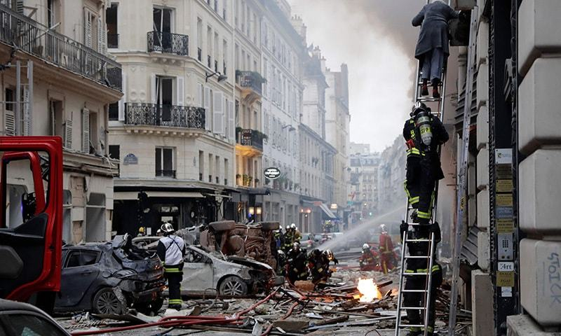 A woman is evacuated by firefighters from an apartment after the explosion of a bakery on the corner of the streets Saint-Cecile and Rue de Trevise in central Paris. — AFP