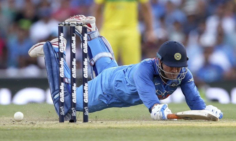 India's M S Dhoni dives to make his ground during a attempted run out by Australia. —AP