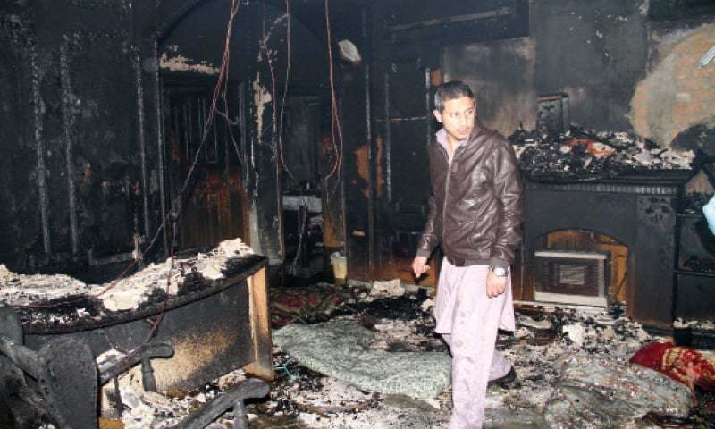 A man stands in the room of the house that caught fire on Tuesday. — White Star