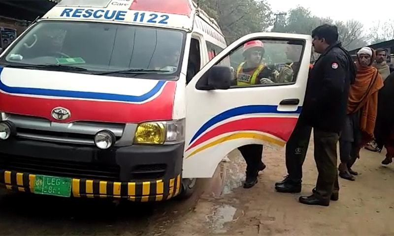Rescue services official talks to police officer outside Pakpattan court, where three people were killed in a firing incident. — File photo