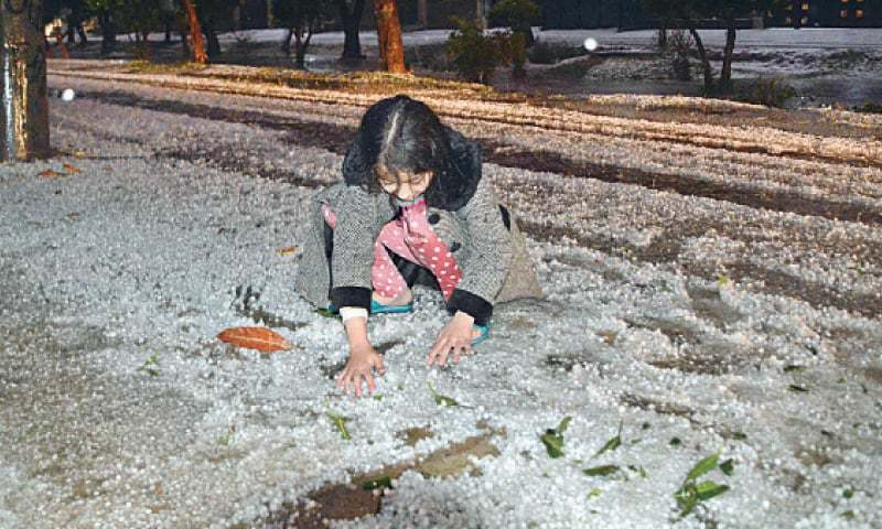 A girl plays with hailstones on a road in Iqbal Town on Tuesday night. — White Star / M. Arif