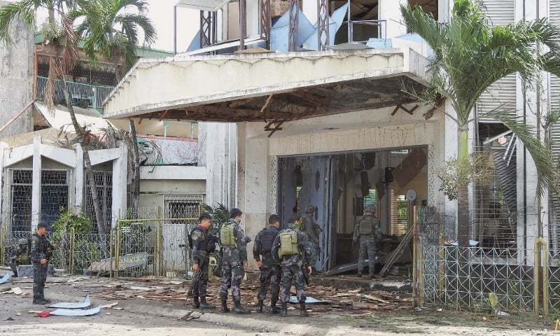 Security personnel inspect the damage caused by the blasts.—AFP