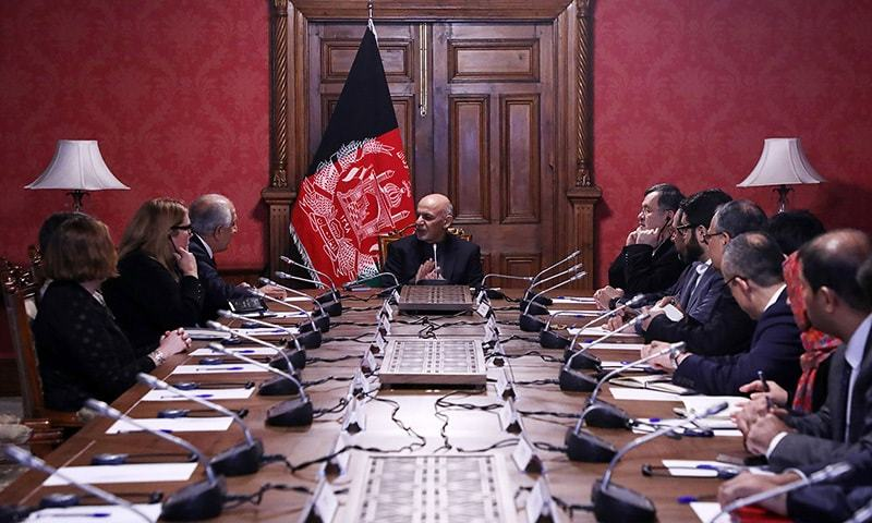 Afghan president Ashraf Ghani (C) talks with US special representative for Afghan Peace and reconciliation Zalmay Khalilzad (top L) during a cabinet meeting at the presidential palace in Kabul. — AFP