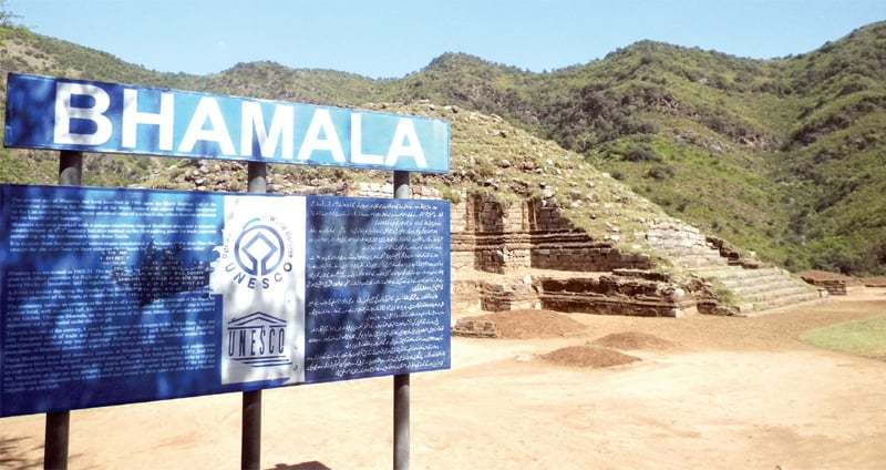 A signboard with information about the Bhamala stupa and monastery in English and Urdu.
