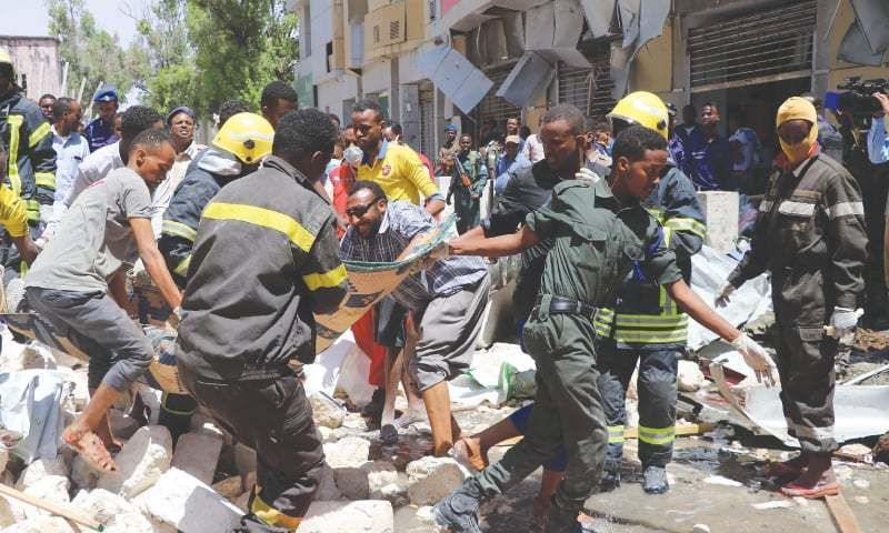 Mogadishu: Emergency rescue staff carry the body of a victim over rubble at the scene of a car-bomb attack on Monday.—AFP