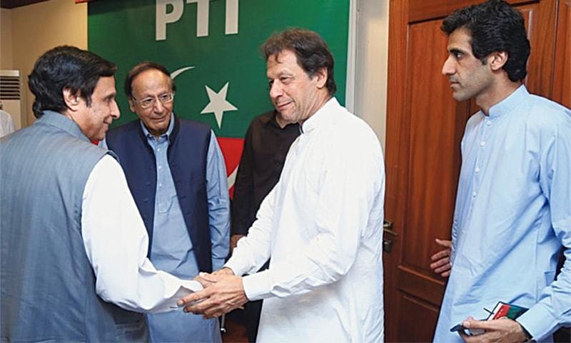 PTI chairman Imran Khan shakes hands with PML-Q leader Chaudhry Pervaiz Elahi at Banigala as Chaudhry Shujaat looks on. — File photo