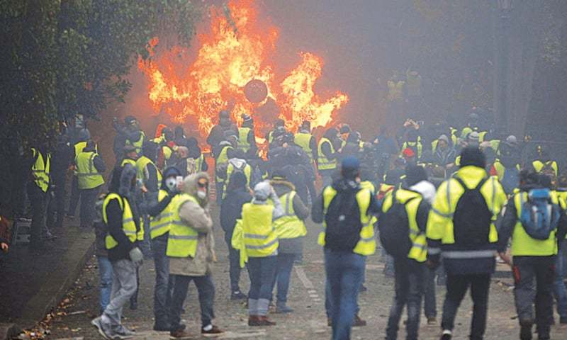 Protestors in yellow vests stand near a burning vehicle. Alain Bertho's book comes out at a time when unrest in his country is resulting in scenes of rioting in Paris reminiscent of the Third World | Reuters