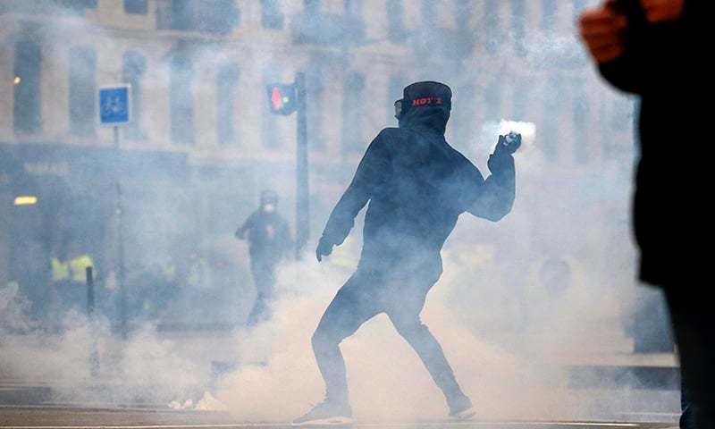 مظاہرین پولیس کی جانب آنسو گیس کا شیل واپس پھینک رہے ہیں — فوٹو: اے ایف پی