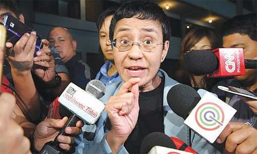 Maria Ressa speaks to the media at the National Bureau of Investigation after her arrest on Wednesday. — AFP