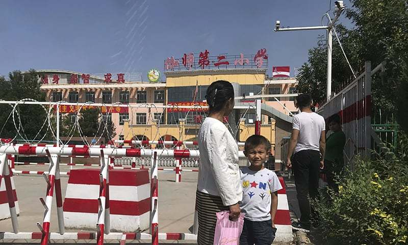 In this Aug. 31, 2018, file photo, a child and a woman wait outside a school entrance mounted with surveillance cameras and barricades with multiple layers of barbed wire in Peyzawat, western China's Xinjiang region. — AP