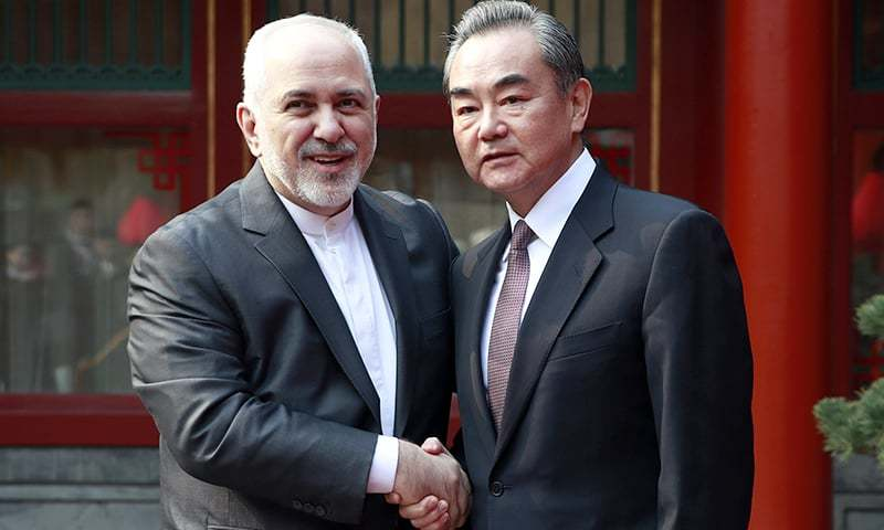 Iranian Foreign Minister Mohammad Javad Zarif, left, and his Chinese counterpart Wang Yi shake hands during their meeting at the Diaoyutai State Guesthouse in Beijing on Feb 19, 2019. — AP