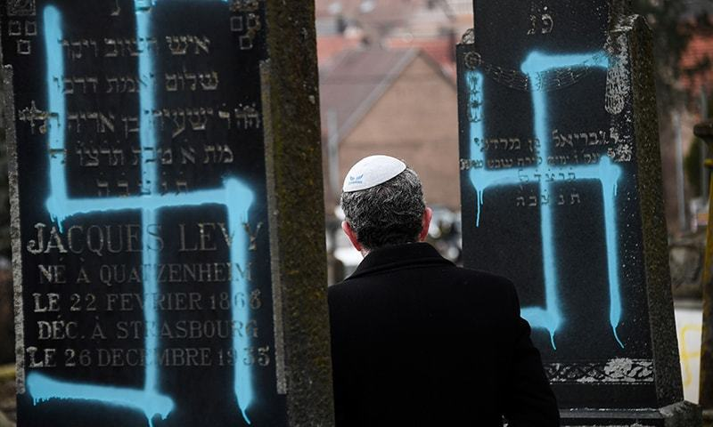 A man walks by graves vandalised with swastikas at the Jewish cemetery in Quatzenheim, on February 19, 2019, on the day of a nationwide marches against a rise in anti-Semitic attacks.  — AFP
