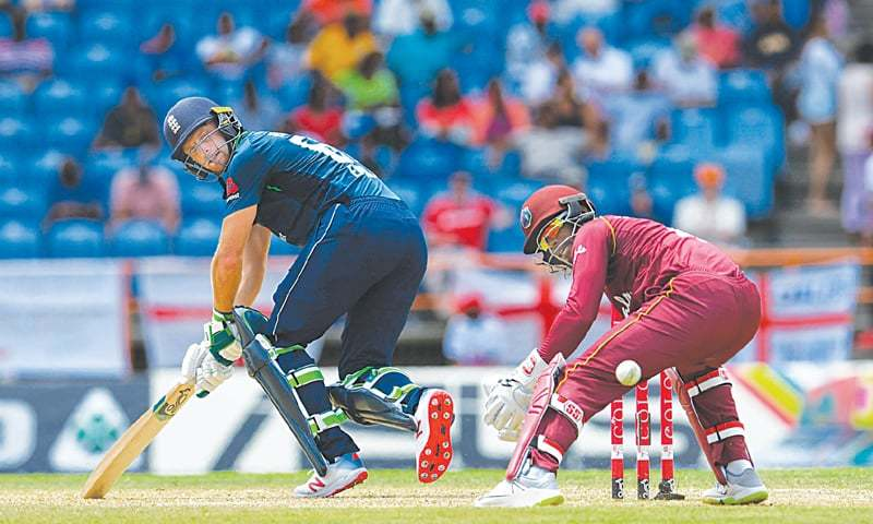 ENGLAND batsman Jos Buttler plays a shot past  West Indies wicket-keeper Shai Hope during the fourth One-day International at the Grenada National Cricket Stadium.—AFP