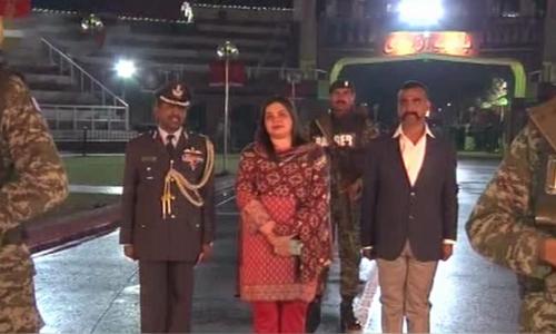 Wg Cdr Abhinandan with Foreign Office Director (India) Dr Fareha Bugti at Wagah border on Friday night. — DawnNewsTV