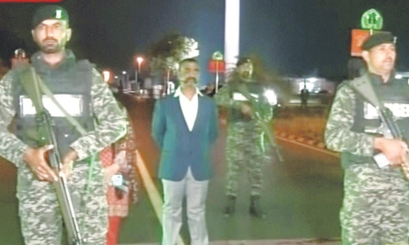 LAHORE: IAF Wing Commander Abhinandan Varthaman (left) waits for his return to India at the Wagah border crossing on Friday night and (right) an Indian convoy is seen transferring the pilot on the outskirts of the northern city of Amritsar, after he was handed over by Pakistani officials.—Reuters