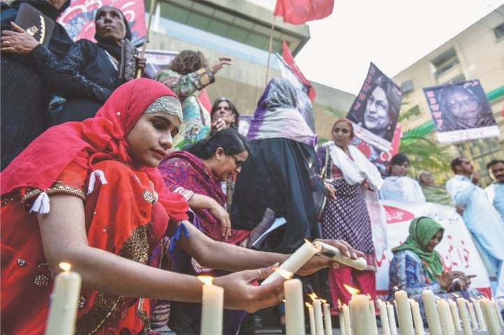 A YOUNG woman lights candles at the vigil outside the press club on Thursday. —Fahim Siddiqi / White Star