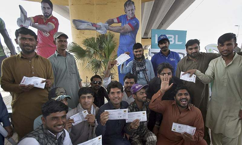 Fans show their tickets upon arrival at National Stadium ahead of the PSL match in Karachi on  Saturday, March 9, 2019. — AP