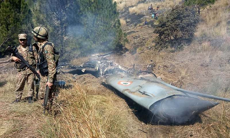 Pakistani soldiers stand next to the wreckage of an Indian fighter jet shot down on February 27, 2019, in Bhimbar district near the Line of Control | AFP