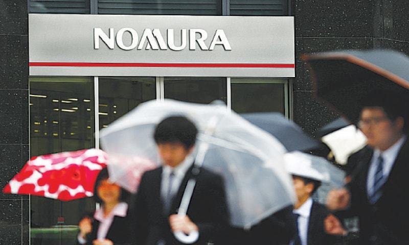 People walk past a branch of the Nomura financial services group in Tokyo.—Reuters