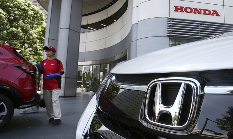 In this July 31, 2018 file photo, an employee of Honda Motor Co. cleans a Honda car displayed at its headquarters in Tokyo.  — AP