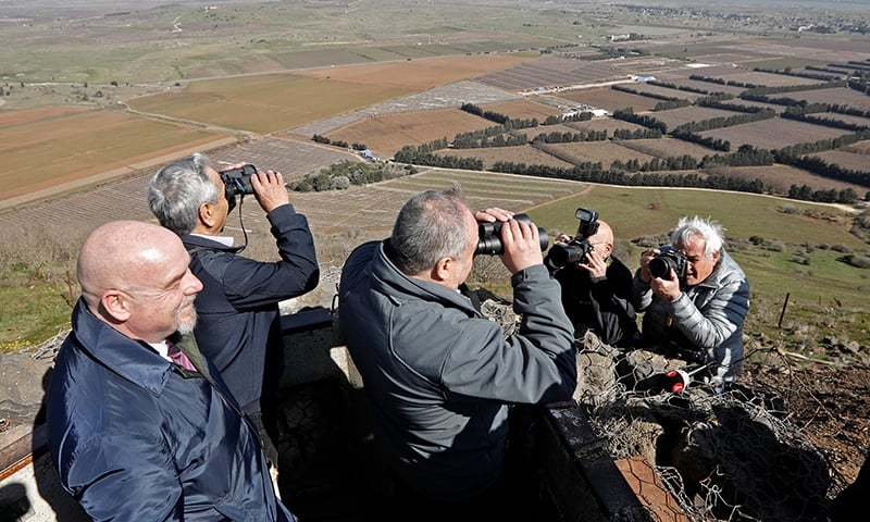 """In this file photo taken on February 5, 2019 Avigdor Lieberman, Yisrael Beiteinu party leader and Israel's former defence minister, looks through binoculars during a visit to a looking point in Mount Bental in the Israeli-occupied Golan Heights, as part of his campaign for the upcoming Israeli election.  The US no longer refers to the Golan Heights as an """"Israeli-occupied"""" territory in its latest annual human rights report, published on March 13, 2019. — AFP"""