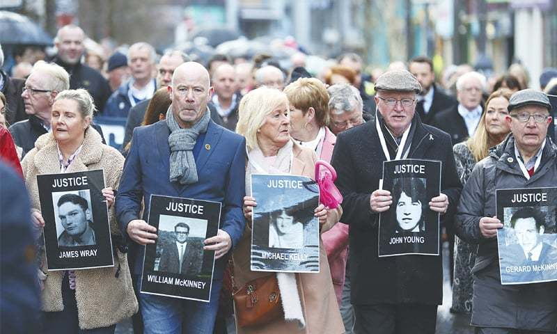 Londonderry (Northern Ireland, UK): Families hold photographs of the victims of Bloody Sunday and march through the Bogside in Londonderry on Thursday.—AP