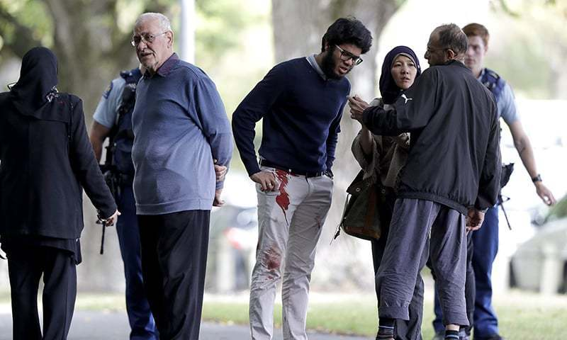 People stand across the road from a mosque in central Christchurch after the attack. — AP