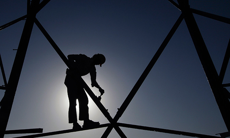 A worker is seen on an electricity tower in Karachi.— Reuters/File