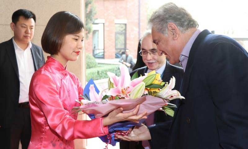 Chinese Ambassador to Pakistan Yao Jing welcomes Shah Mahmood Qureshi with flowers. — Photo courtesy: PID Twitter account