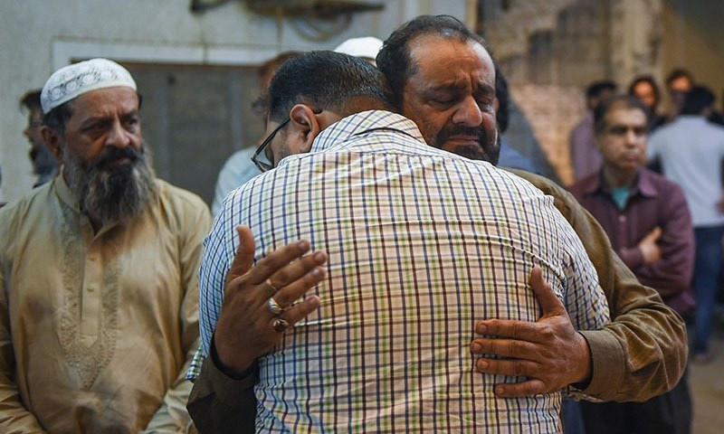 A Pakistan man embraces the father of Syed Areeb Ahmed (R), reportedly gunned down in the New Zealand massacre, in Karachi on March 16, 2019, a day after the shooting attack on two mosques in Christchurch. — AFP