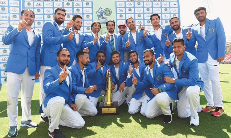 DEHRADUN: Afghanistan players pose with the trophy after winning the Test against Ireland at the Rajiv Gandhi International Cricket Stadium on Monday.—AFP